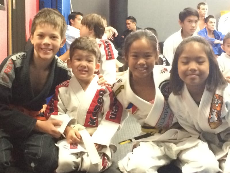 Kai smiling with 3 younger kids all in their jiu jitsu uniforms