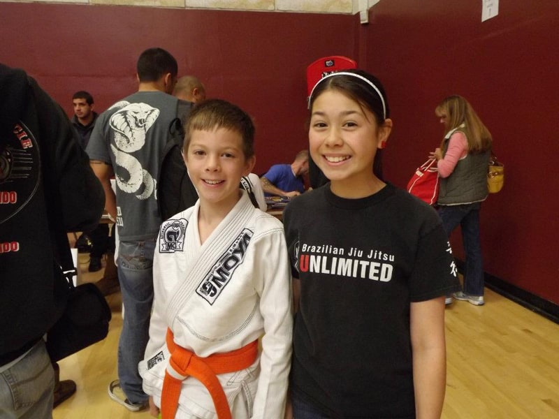 Kai in his Jiu Jitsu uniform smiling with another young girl